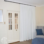 White box pleat curtains on a black rod