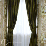 Dark green silk curtains and pelmets with white sheers