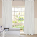 White box pleat blockout curtains on black rods