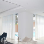Translucent white s-fold curtains in a recess