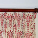 Embroidered goblet pleat curtains on stained timber rods