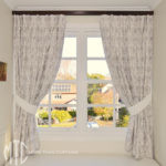 Embroidered pinch pleat curtains on stained timber rods with tiebacks