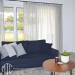 Grey s-fold sheer curtains on a black rod