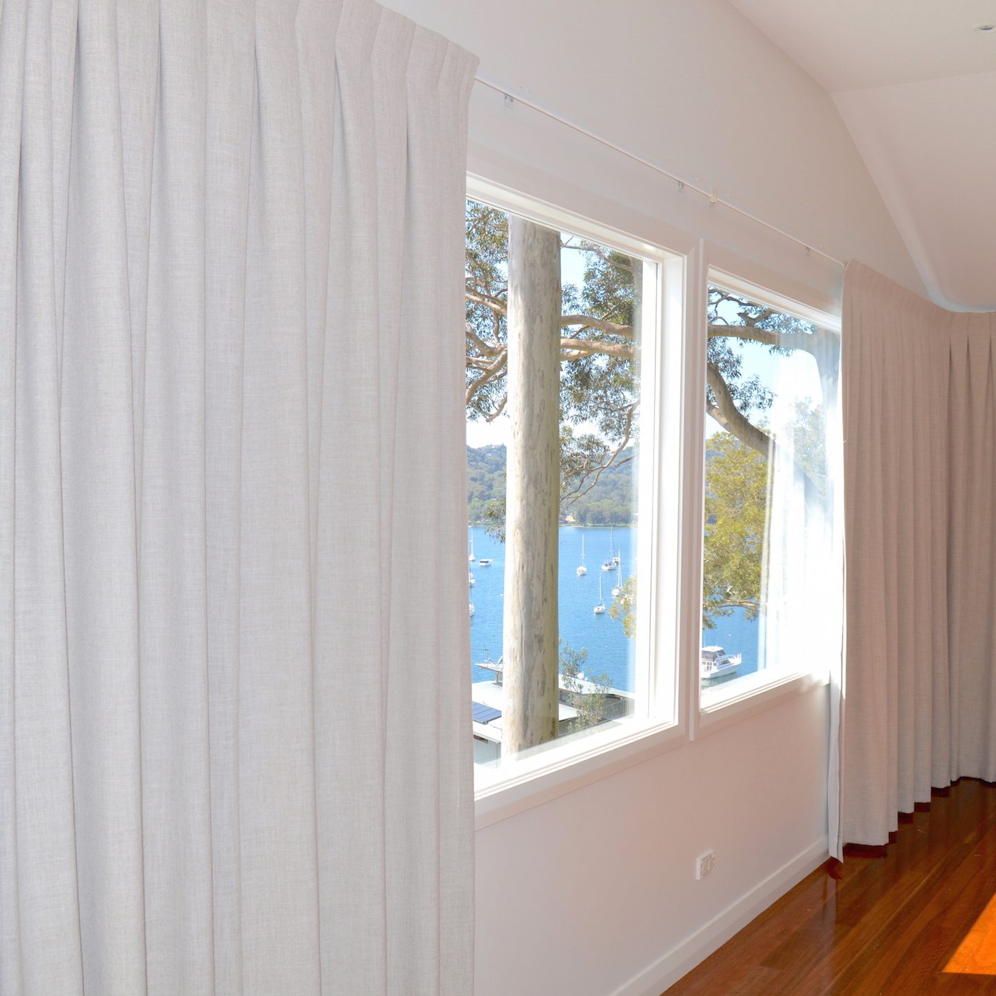 Beige box pleat curtains on a corner window