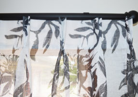 Leaf patterned double pinch pleat sheer curtains on black rods