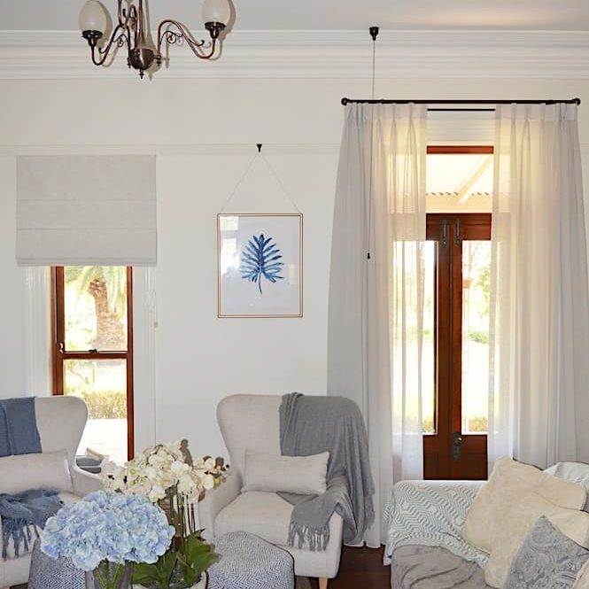 Triple pinch pleat sheer curtains on rods with matching Roman blind
